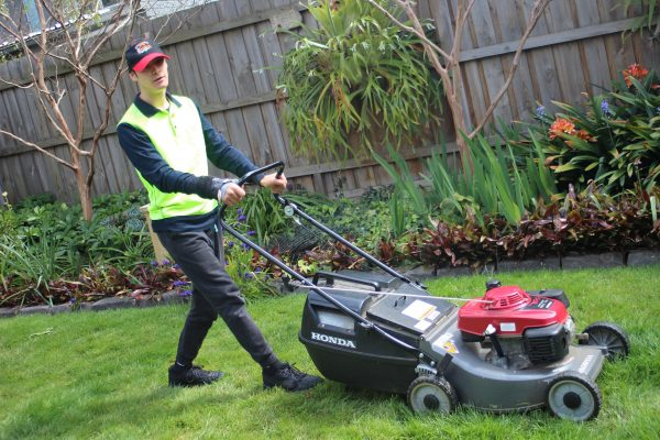 A young man in a baseball cap and high-vis vest mowing the lawn
